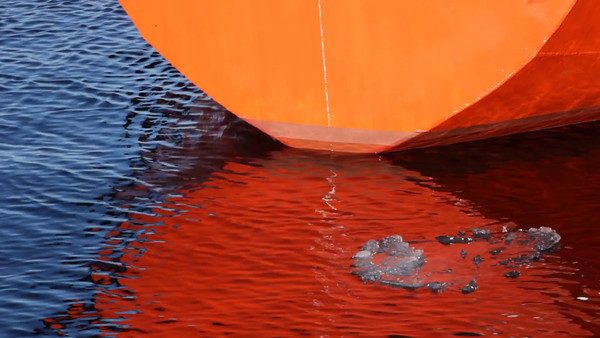 Isflak och skepp - A small ice floe passes the metal hull of a boat.