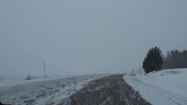Köra bil på vintern - Pov: driving on a snowy coutry road through rural landscape on a gray winter day