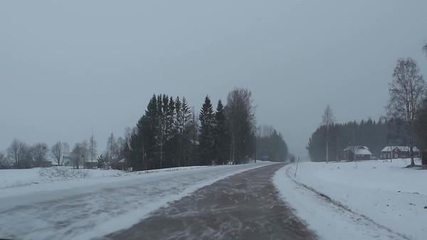 Bilfärd på vinter väg - Driving through a village when snow stirred up by oncoming truck obscures sight