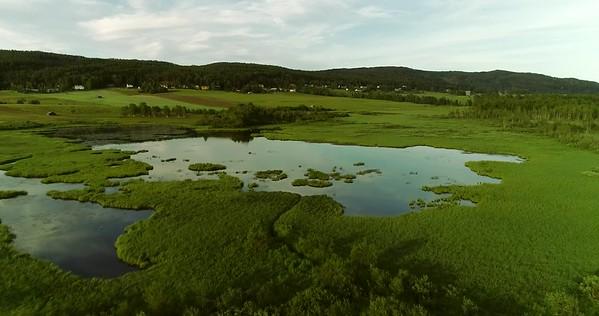 Östansjösjön och Gottne från ovan -  Aerial: flight over meadows towards a lake in a wide valley