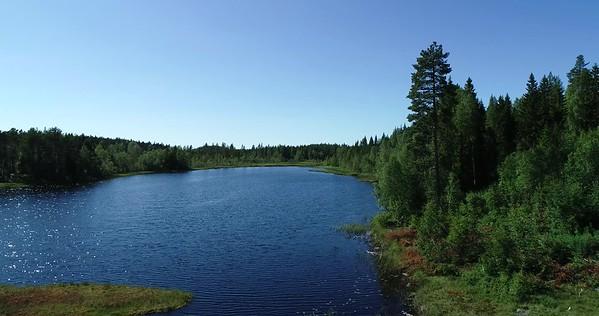 Bodsjön från ovan -  Aerial: flight parallel to the shore of a lake with a footbridge