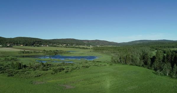 Östansjösjön och Gottne från ovan -  Aerial: flight over meadows towards a lake in a valley surrounded by hills