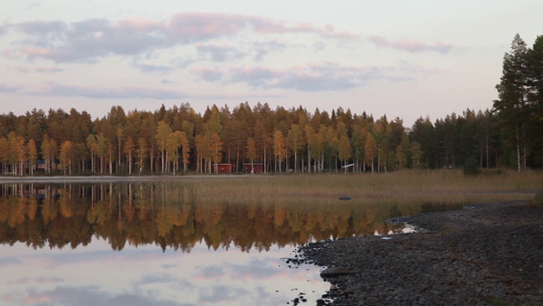 Myckelgensjösjön på hösten -  Pan over a lake shore with wooden lodges