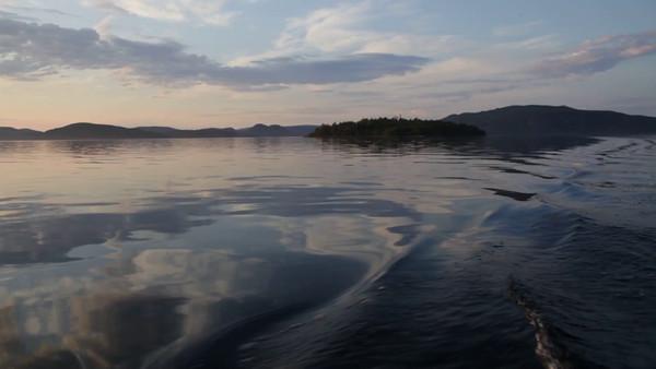 Med båten på Gaviksfjärden i sommaren -  Traveling in a small boat past an island at sunset