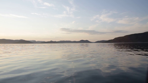 Med båten på Gaviksfjärden i sommaren -  Travelling in a small boat on the smooth waters of a bay while the sun is settin