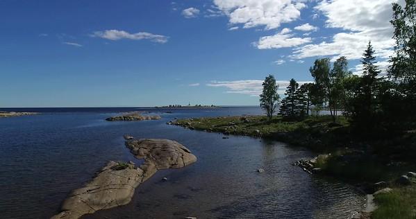 Järnäsklubb på sommaren -  Aerial: flying over an inlet towards the open sea at low height
