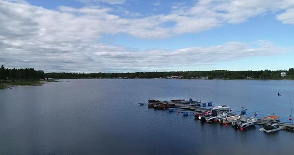 Järnäsklubb på sommaren -  Aerial: rising over a jetty with a fluttering hawk kite