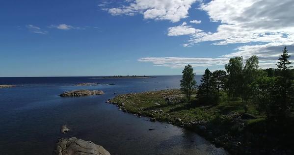 Järnäsklubb på sommaren -  Aerial: flying backwards over an ocean bay and over two white birds