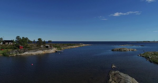 Järnäsklubb på sommaren -  Aerial: fast pan from the ocean over a road to a bay