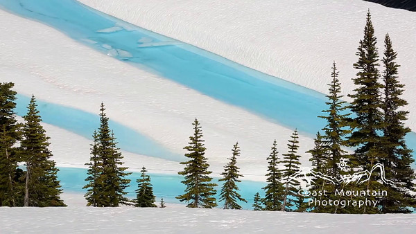 Bright blue water appearing in a reservoir during snow melt on Whistler Mountain Stock video footage by Mitch Winton - coastphoto.com