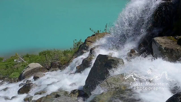 Close up of a glacier fed waterfall with emerald coloured water behind. Shot in Joffre Lakes Provincial Park, BC, Canada Shot at 60fps Stock video footage by Mitch Winton - coastphoto.com