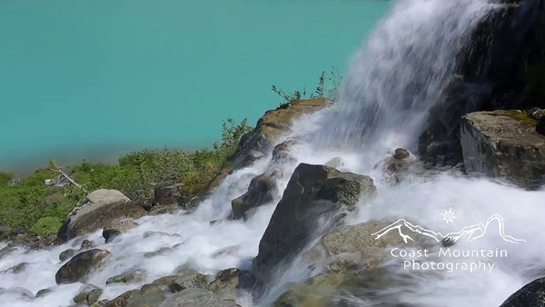 Close up of a glacier fed waterfall with emerald coloured water behind. Shot in Joffre Lakes Provincial Park, BC, Canada Stock video footage by Mitch Winton - coastphoto.com