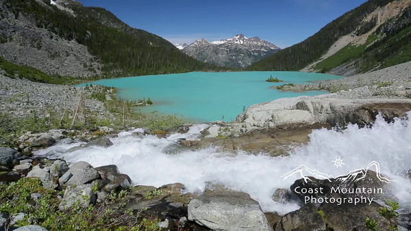 Glacier fed waterfall with emerald coloured lake behind. Shot in Joffre Lakes Provincial Park, BC, Canada Stock video footage by Mitch Winton - coastphoto.com