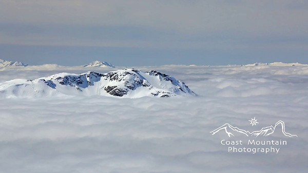 A pan past Whistler Mountain to Black Tusk with both just appearing out of the valley cloud