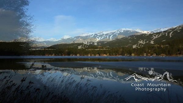 A pan over a partially frozen Alta Lake in afternoon light with Blackcomb Mountain reflection Stock video footage by Mitch Winton - coastphoto.com