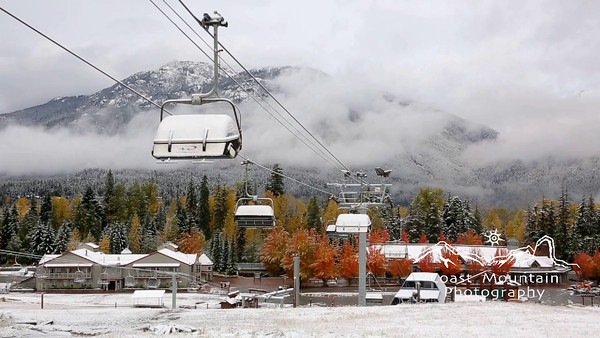 The Upper Village of Whistler during Fall. Wizard chair and Sproat Mountain covered in snow with coloured leaves on trees. Stock video footage by Mitch Winton - coastphoto.com