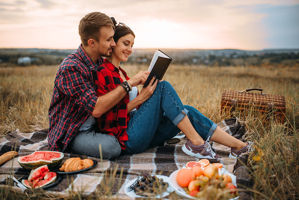 Couple reads book together, picnic on the grass