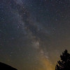 The Milky Way rotates through the sky as clouds reflect the light from Ogden Utah. A few Persied meteors are visible.