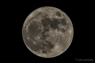 A plane passing in front of the Full Moon
