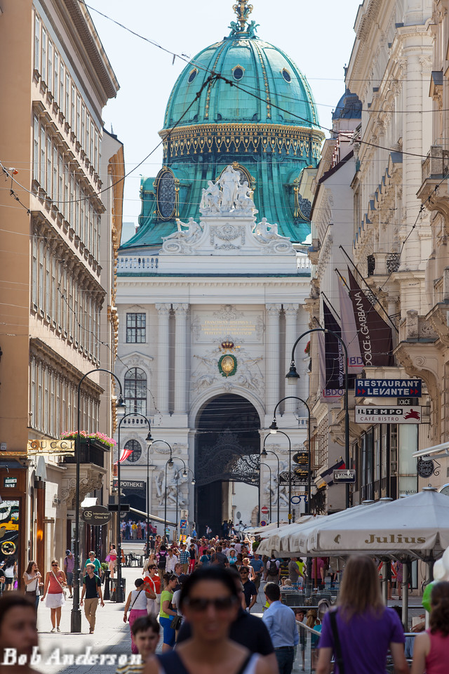 """Tourists traveling through Michaels Wing in the Hofburg complex, with a very ornate and beautiful statue above. <br /> <br /> The statue is the Personification of Wisdom and is flanked by the allegory of Justice on the right and Power in the person of Hercules on the left. The sculptor"""" Johannes Benk"""