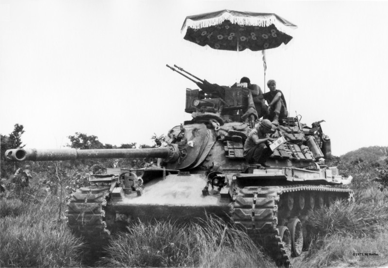Blackhorse Troopers check map coordinates from the deck of their M48A1 Patton Tank just a few kilometers east of the Cambodian border in March, 1971 . This photo was published in 2007 with the permission of the photographer in a United Kingdom edition about umbrellas. © 1970, MJ Roche.