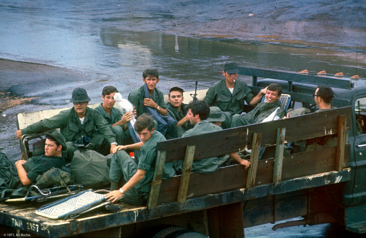 "A group of REMF's head out to all-night guard duty on the wire at Long Binh.  A REMF is a ""Rear Echelon Military Folk"". Other translations were more prevalent."