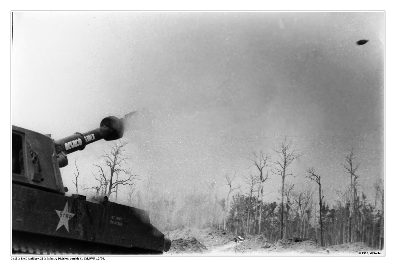 Overlooking the Michelin rubber plantation just west of Cu Chi a 155mm self-propelled howitzer fires a round in support of 25th Infantry Division troops  (3/13th Artillery Battalion).  Photo by Mike Roche with an Asahi Pentax Spotmatic, one of the first, popular 35mm single lens reflex cameras, with TriX Pan 400 ISO film (by Mike Roche in October 1970).