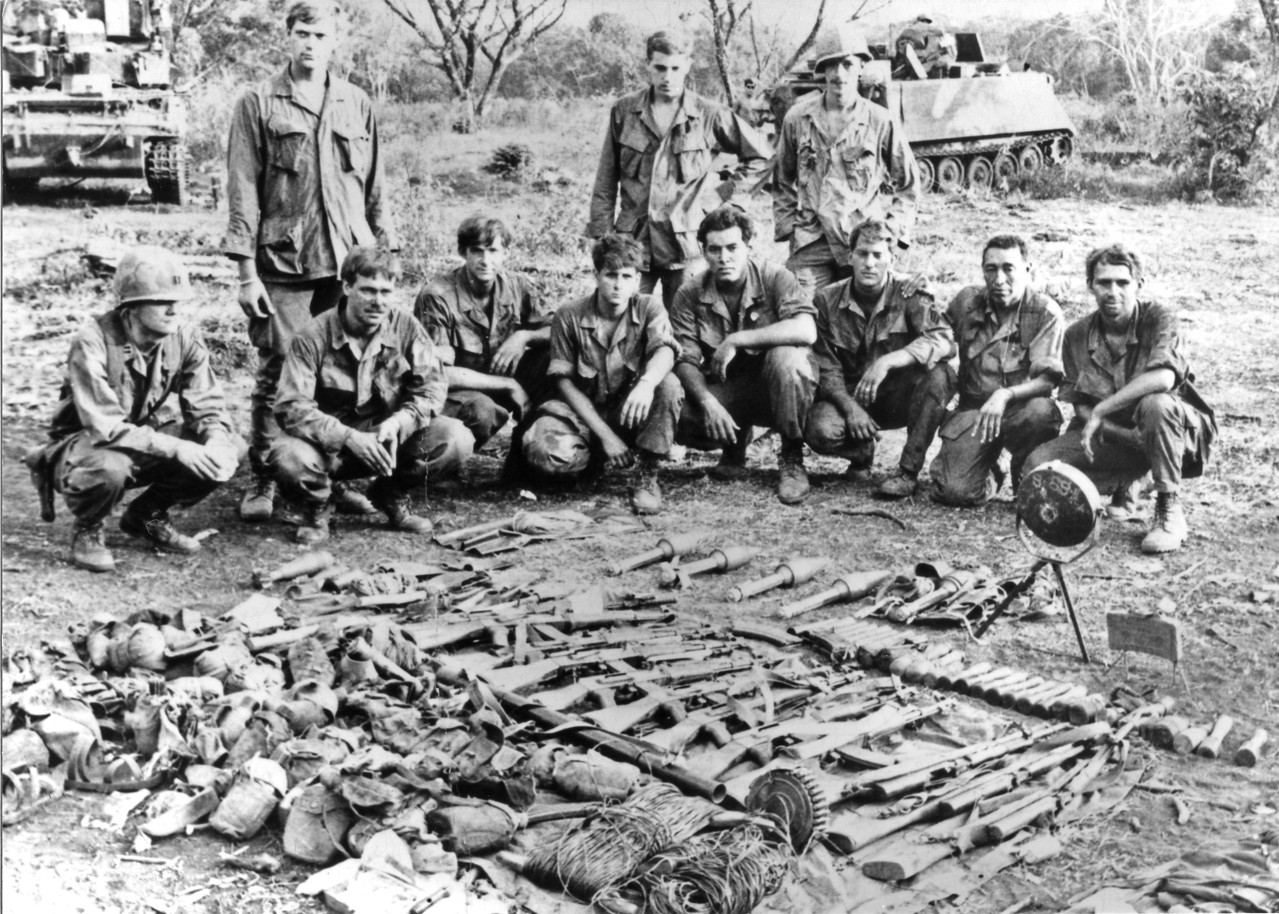 """The Things They Carried"" after the Tim O'Brien novel of the same name.  A cache of weapons discovered in a tunnel complex by Blackhorse Troopers, in February, 1971, near Trang Bang village (11th Armored Cavalry Regiment photo).  Satchel charges, grenades, several rifles, RPG rounds, and anti-personnel devices."