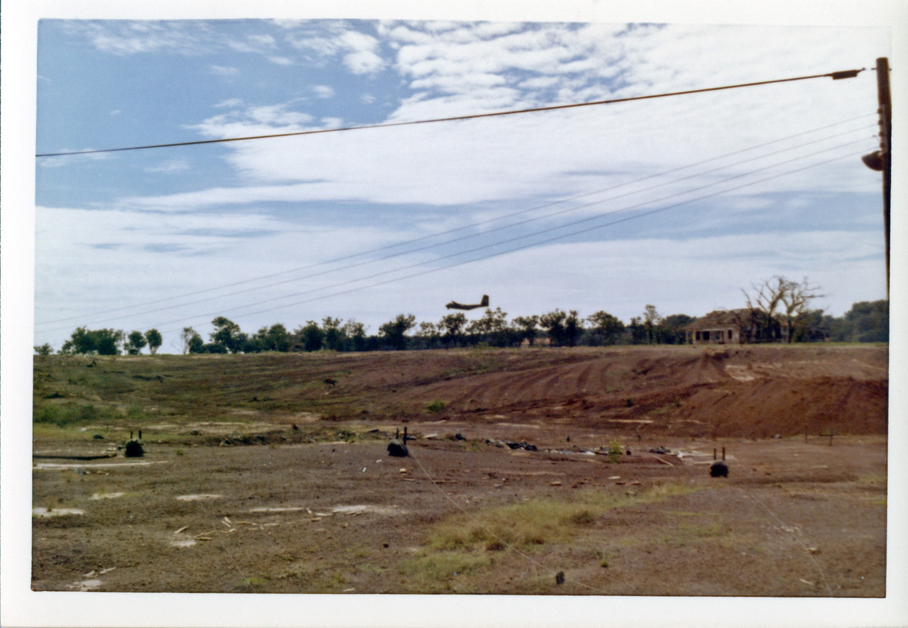 A C-130 cargo plane lands at the US Army airstrip at Bien Hoa.  US claymore mines are shown in the foreground.