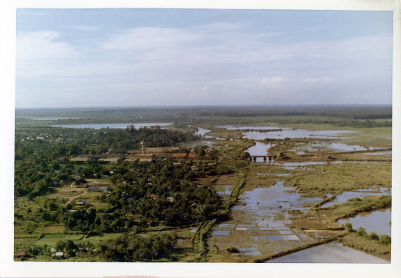 A small village and rice paddies seen from a Huey (Bell UH1) helicopter on a mail delivery flight to Nui Ba Den.