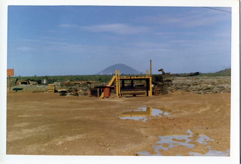 Nui Ba Den (Black Virgin Mountain) in Tay Ninh Province stands over 3200 feet tall.  Seen here from a small fire support base (11th Armored Cavalry Regiment).  The extinct volcano had a US Communications base near the summit and was sprinkled with VC caves throughout the center elevations.  © 1971, MJ Roche.