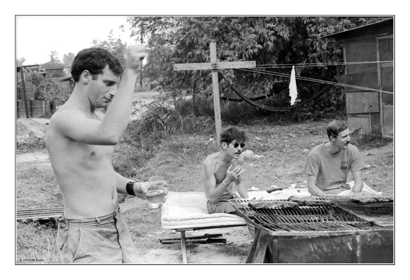 Jeff Lowe, Bob Eveler and Paul Mahoney behind the hooch at Di An, barbecuing beef from PX. © 1970, MJ Roche.