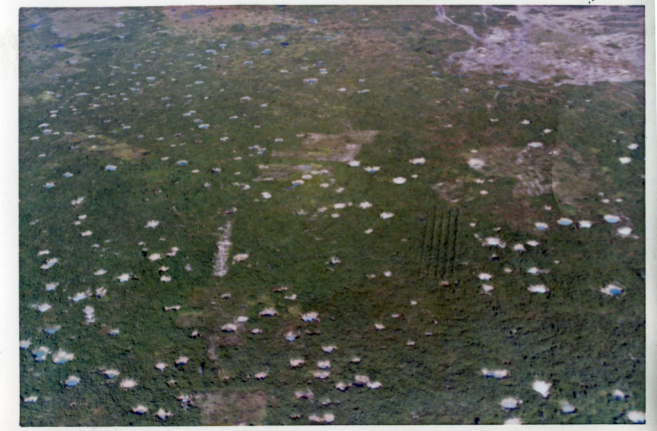 """The pock-marked countryside outside of Cu Chi where the 25th Infantry Division basecamp was located.  Seen from a Huey helicopter in September 1970.  Many of these """"pools"""" were later used by the Vietnamese for fish farming.  Unexploded US Ordinance is still being found in 2015 throughout the Vietnamese countryside."""