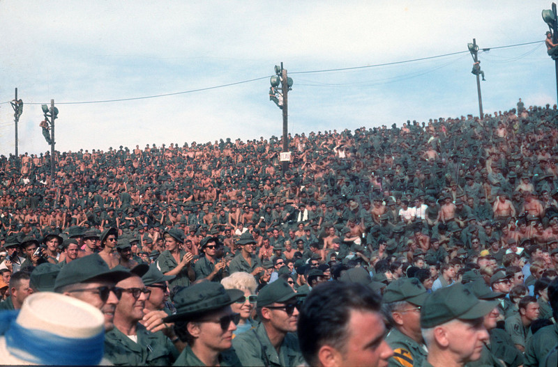 Long Binh audience at the Christmas Day Bob Hope Show. You will note the American civilian women in the audience.  These were the spouses of senior military from units in the Saigon area! Thanks for that memory! © 1970, MJ Roche.