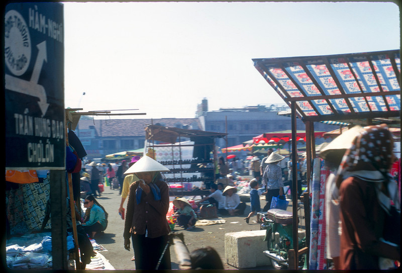"""Saigon street market captured in January 1971. Directional sign indicates upcoming intersection.  """"Cholon"""" is a Saigon neighborhood populated by the ethnic Chinese.© 1971, MJ Roche."""