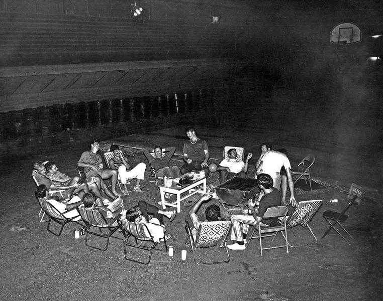 "The nightly ""Circle"" at Long Binh between the hooches, next to the basketball pad. On this night I was given a lesson in how to drink fine wines properly. The tipped chair, far right,  came from the 557th LE Engineer Bn., part of the 18th Engineer Brigade. A cassette tape played on the table provided the tunes.  © 1971, MJ Roche."