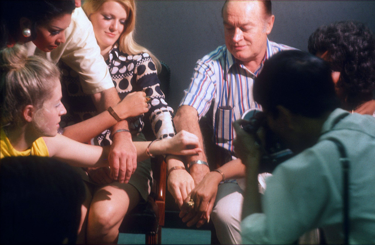 Bob, Gloria Loring, Jennifer Hosten from Grenada (Miss World, 1970), and others show off their POW bracelets at the press conference following the Christmas Day Bob Hope Show at Long Binh, RVN.