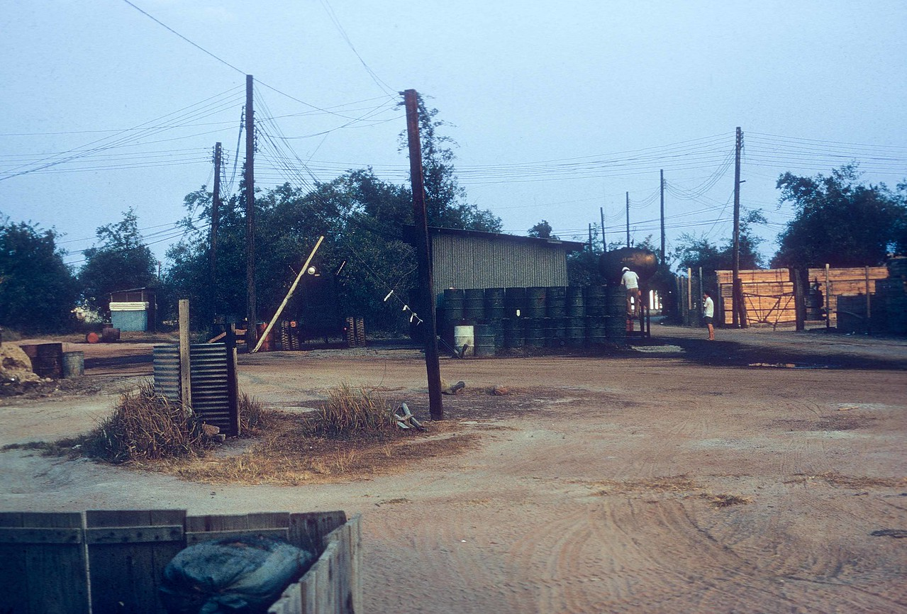 View at Di An, February, 1971.  Generating station. right, with piss tube and latrine at center, left. (11th Armored Cavalry Regiment).  Foreground, left, are the sand bags at the front of the 17th PID  (Public Information Detachment) hooch and office building that were designed to minimize casualties during rocket attacks.   At right, center, two Vietnamese contractors adjust the fuel tanks feeding the source of local electricity.  The noisy generators ran 24 hours a day.