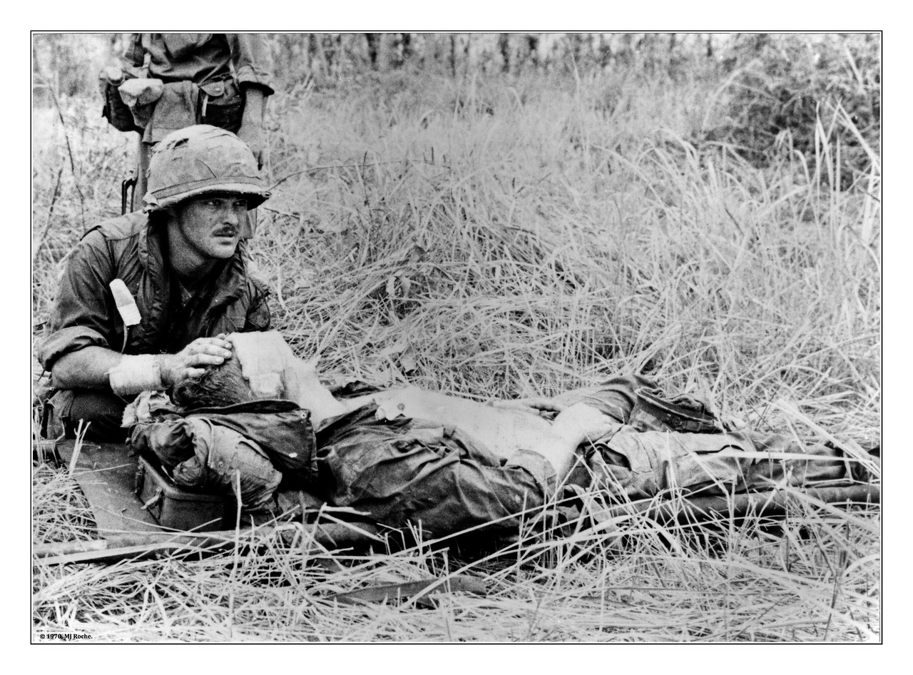"""Hang On"" Awaiting a medevac chopper after a VC mortar round injures a 25th Division infantryman near Tay Ninh in October 1970."