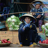 Today's daily travel photo is of  a Vietnamese lady supporting a yoke on her conical hat selling fruit at a local market in Dalat, Vietnam.
