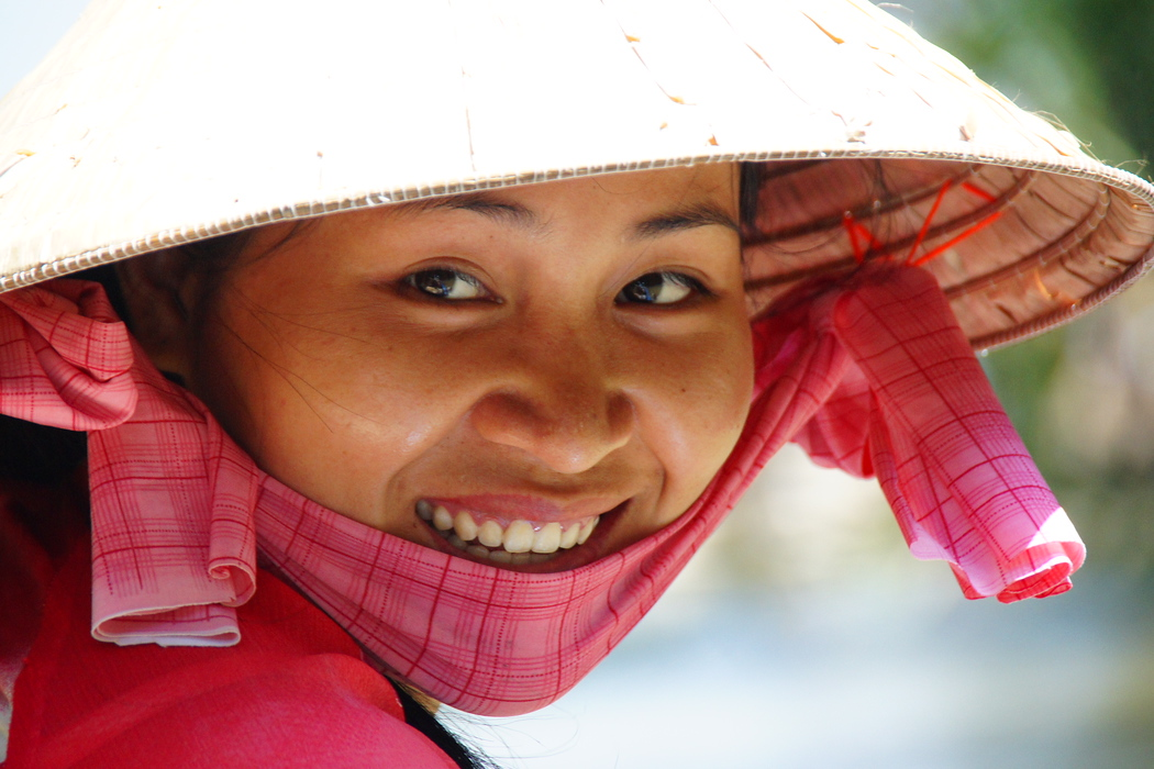 A Vietnamese lady wearing a conical hat radiates a beautiful smile - Mekong Delta, Vietnam.