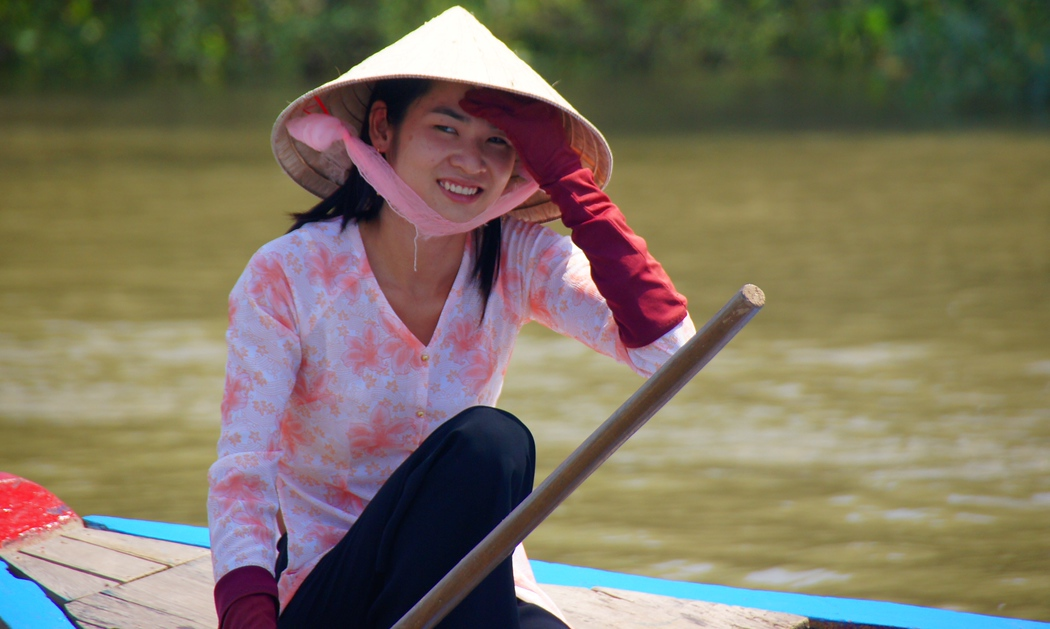 Smiling Lady wearing a conical hat along the Mekong Delta, Vietnam