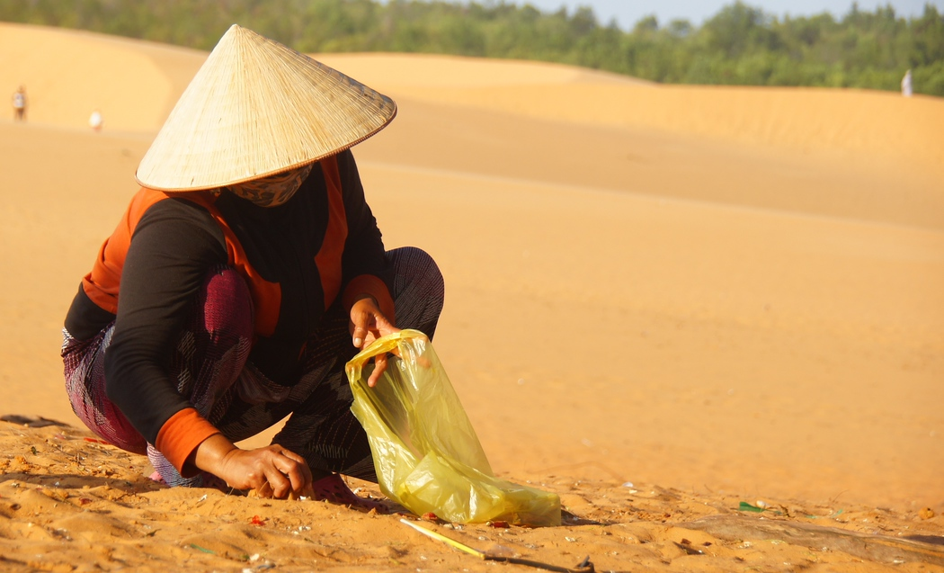 A lady collecting garbage in the sand dunes - Mui Ne, Vietnam.