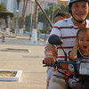 "A family smiles as they whiz down the sidewalk on their scooter - Nha Trang, Vietnam.  Travel photo from Nha Trang, Vietnam. <a href=""http://nomadicsamuel.com"">http://nomadicsamuel.com</a>"
