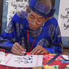 Today's daily travel photo is of a Vietnamese man dressed in traditional silk attire perfecting his craft of calligraphy in Ho Chi Minh City, Vietnam.
