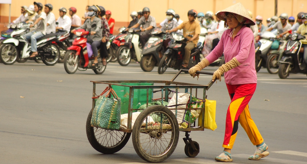 http://nomadicsamuel.com : A local Vietnamese lady pushes a cart across a street amidst a seas of motorbikes stopped at a traffic light: Saigon (Ho Chi Minh), Vietnam.