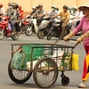 "<a href=""http://nomadicsamuel.com"">http://nomadicsamuel.com</a> : A local Vietnamese lady pushes a cart across a street amidst a seas of motorbikes stopped at a traffic light: Saigon (Ho Chi Minh), Vietnam."