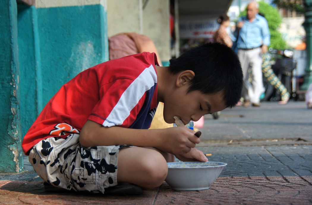 A Vietnamese boy sitting down and eating a bowl of Pho on the side-walk - Saigon, Vietnam.  This is a travel photo from Ho Chi Minh City, Vietnam.