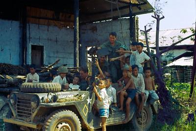 Vietnamese children on gun jeep