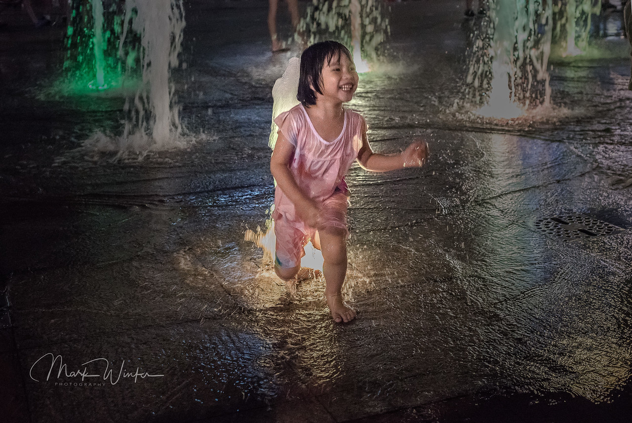 Saigon, Outside the former Presidential Residence, people stroll on a hot summer evening. Colored water fountains spring from the concrete and children walking by with their parents enjoy splashing in the pools.